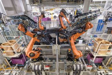 Body in white on assembly line while robots place glass on vehicle body with Sika Assembly Adhesives