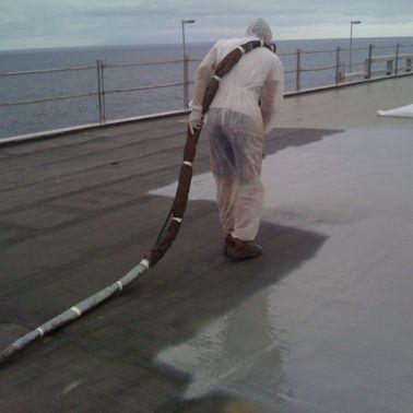 Worker applying waterproofing LAM system at the Barcelona El Prat Airport