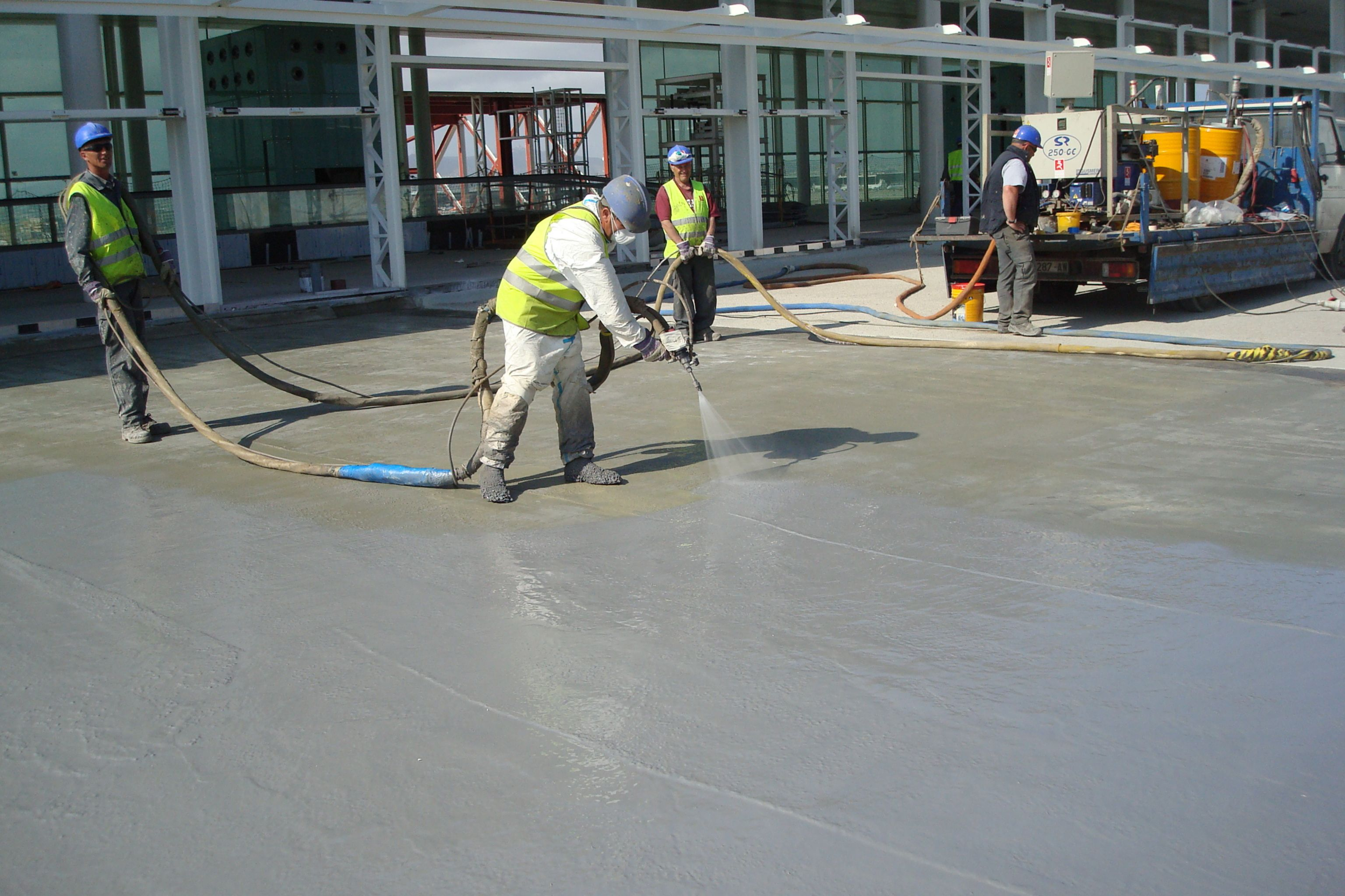 Workers applying waterproofing LAM system at the Barcelona El Prat Airport