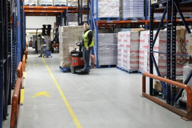 Storage warehouse shelves and floor and worker with palette