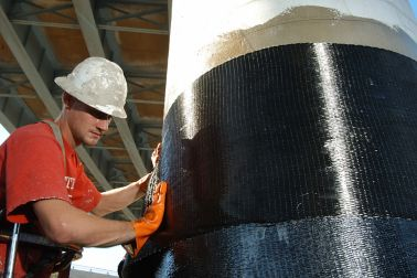 Men applying Sika CarboDur carbon fiber plates for structural strengthening