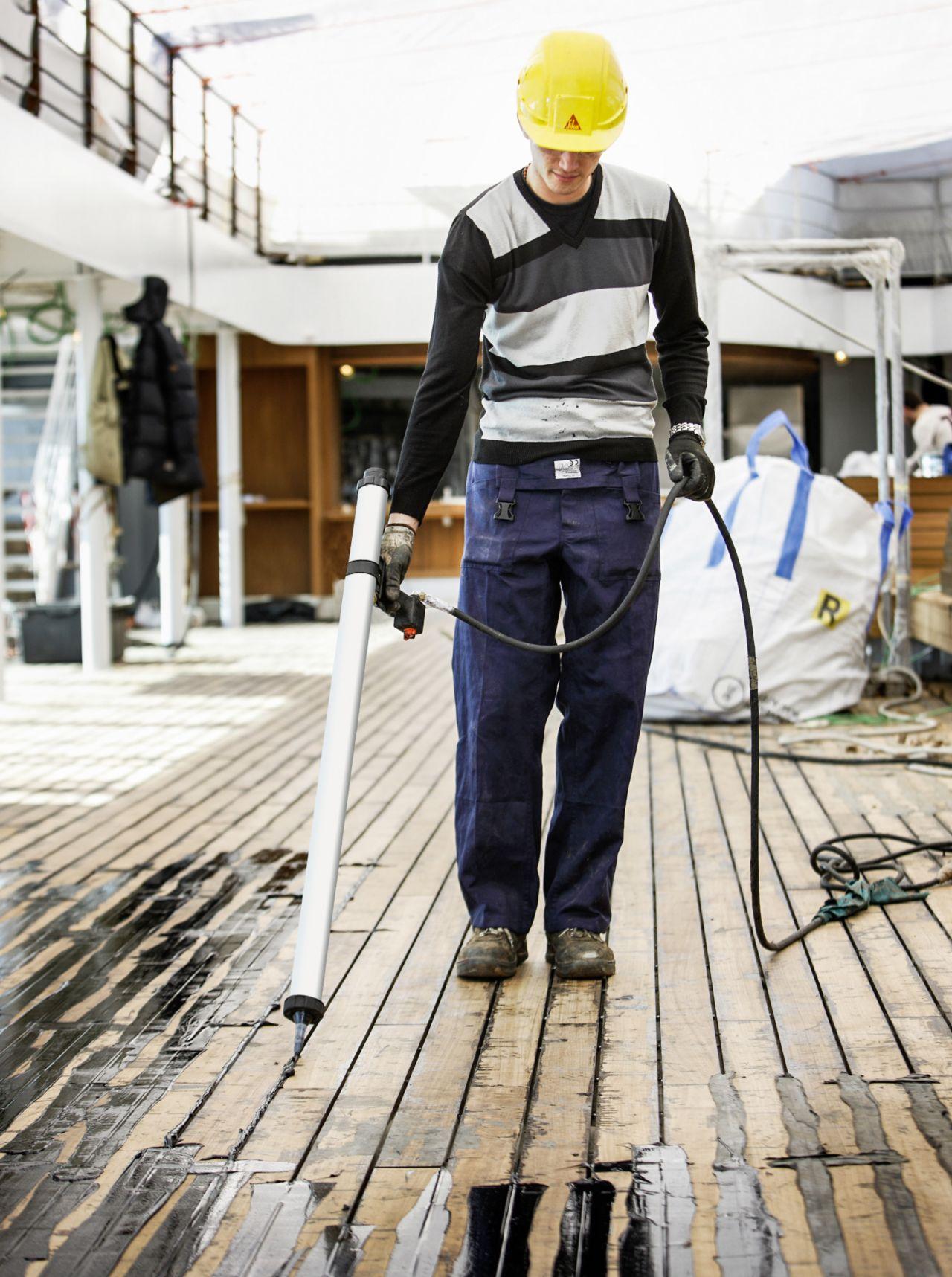 person bonding a teak deck on a yacht