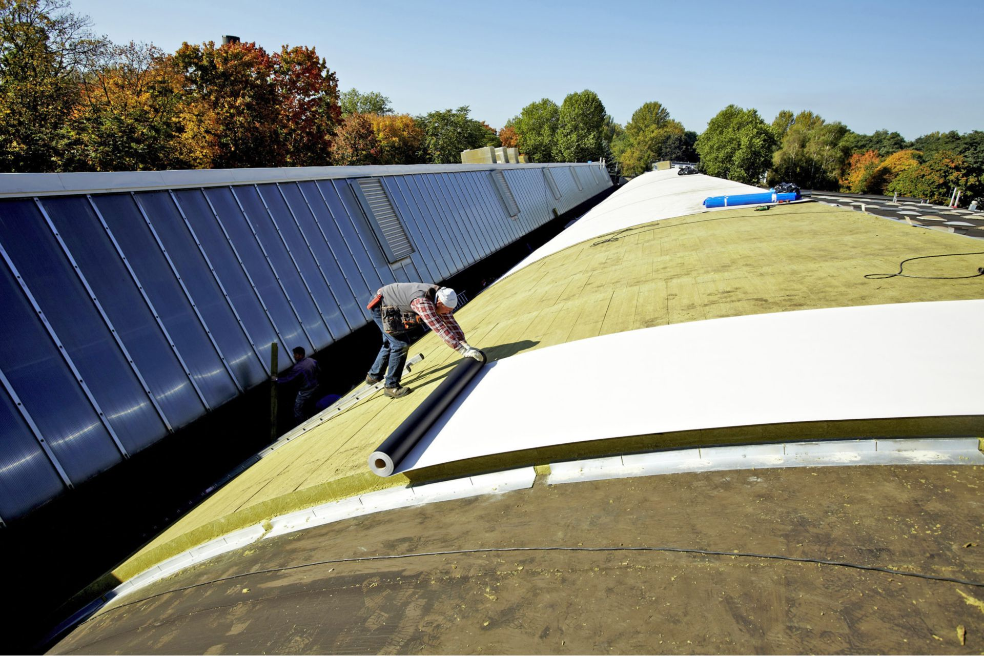 Curved shed roof renovation with Sika mechanically-fastened Sarnafil and Shedrock insulation at Volkswagen Hannover and Wolfsburg, Germany