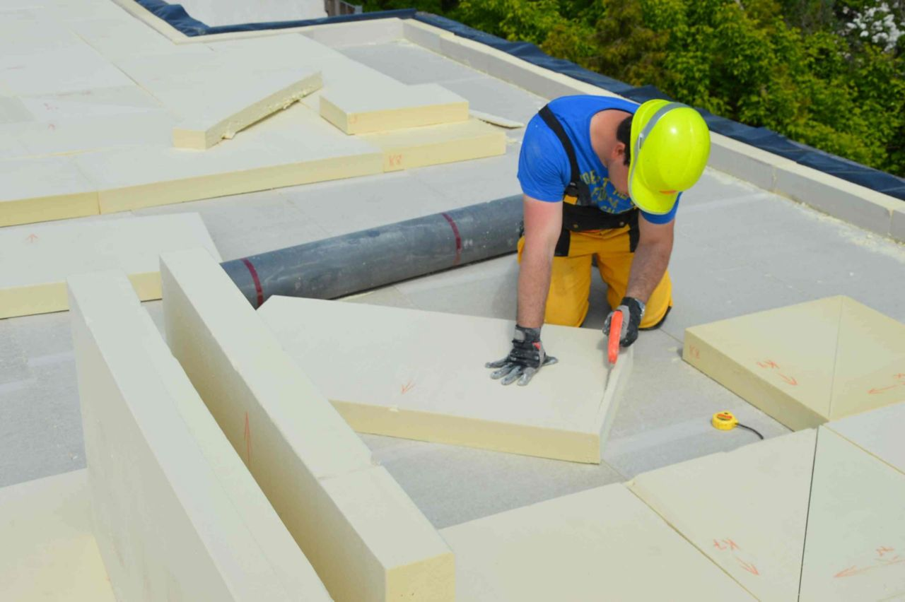 Man cutting installing thermal insulation on a roof