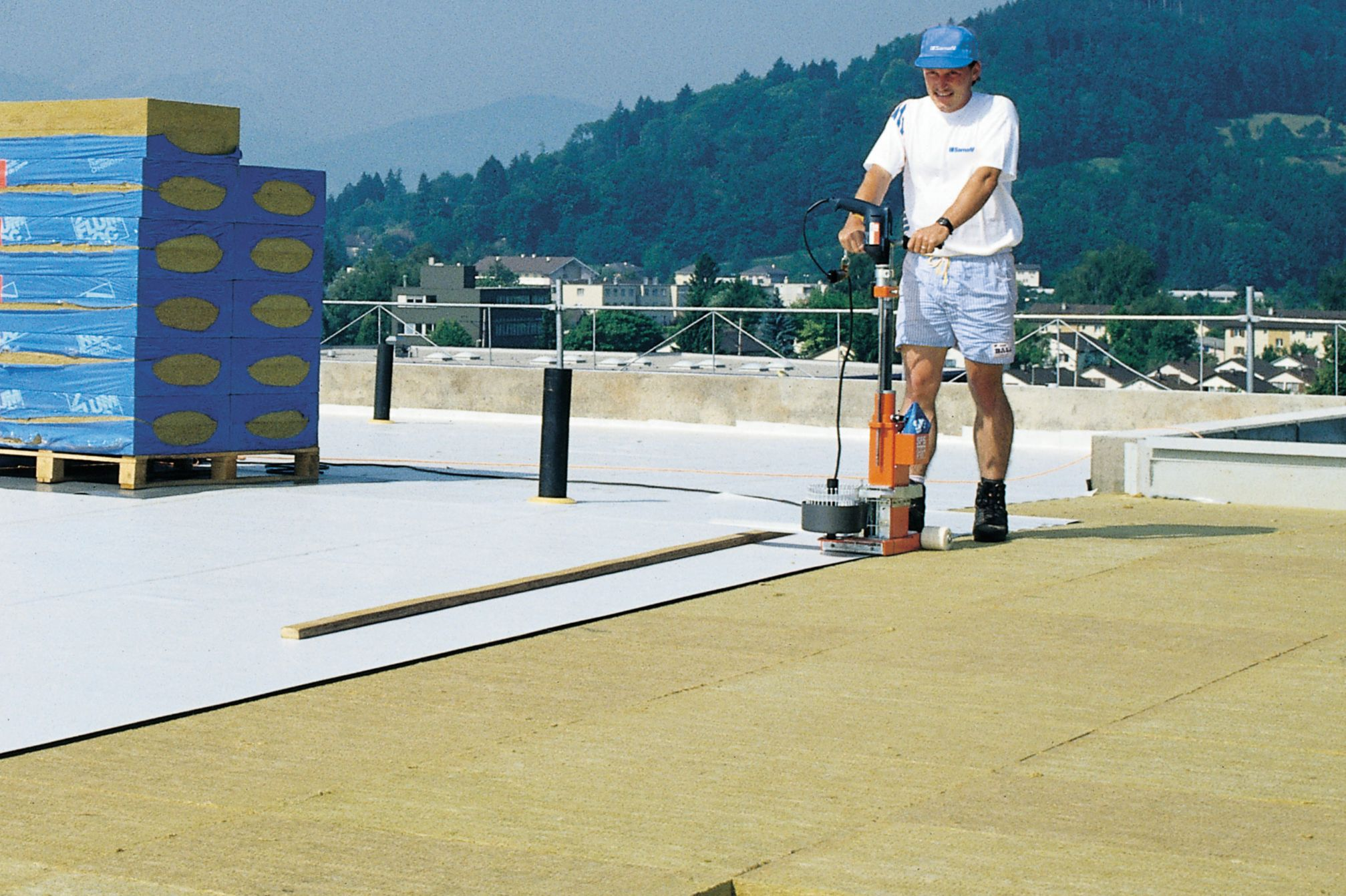 Man installing thermal insulation with a machine