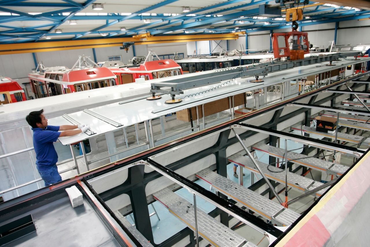Worker and machines assembling trains in manufacturing factory