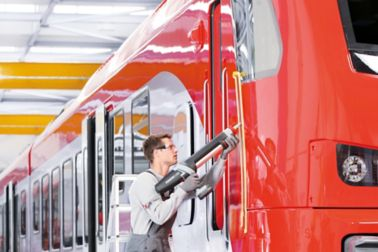 Person applying bonding a train with a powercure dispenser