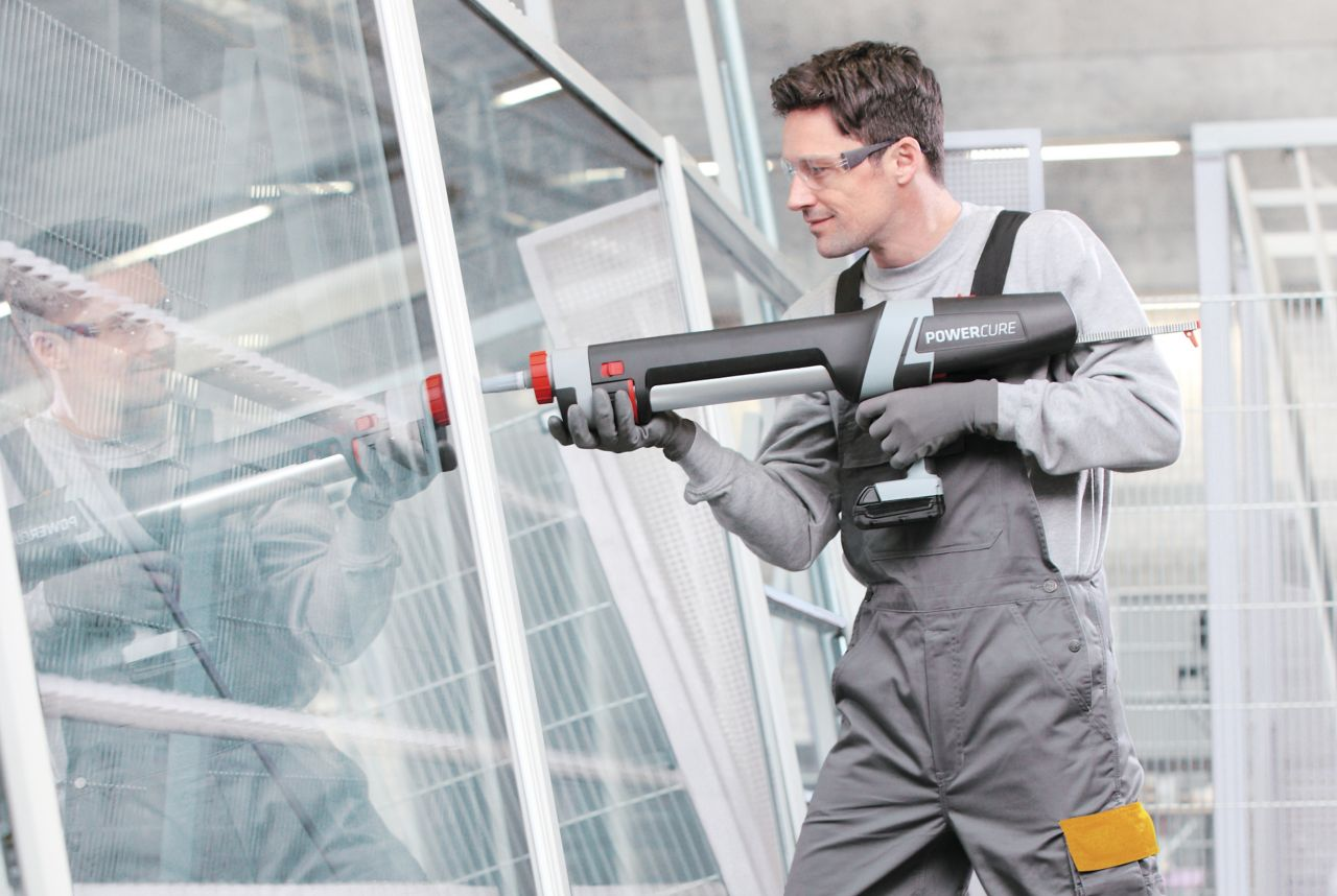 Man assembling a window with PowerCure dispenser