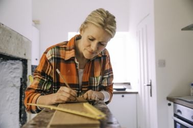 Woman measuring wood for DIY home improvement project