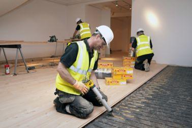 Workers applying wood floor adhesives in a residential building
