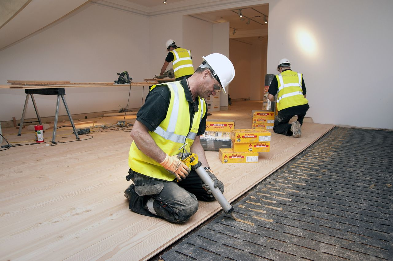 Workers applying wood floor adhesives in a residential building