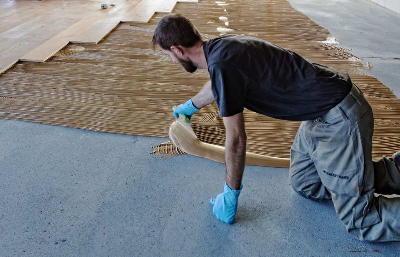 Workers applying wood floor adhesives