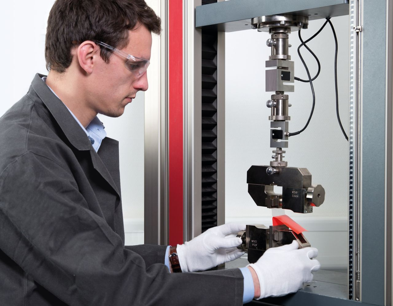 A man performing a tensile strength test on a zwick machine