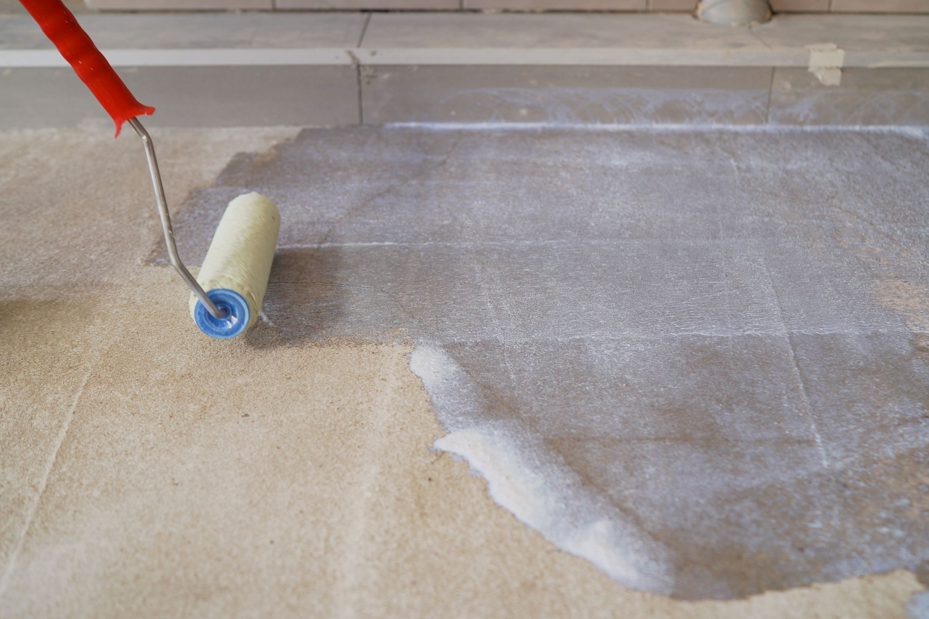 Floor repair using a primer. Priming the concrete floor with a roller. Professional floor primer. Leveling concrete floors.