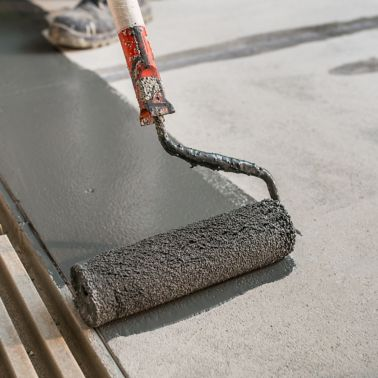 Manual worker installing non slip surface on the floor next to the drain gully