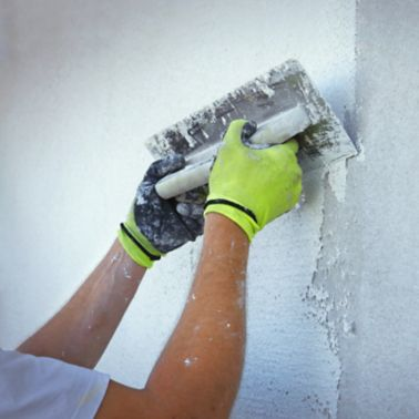 Plasterer making new white plaster with a trowel