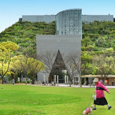Woman walking with her dog in front of ACROS (Asian Crossroads Over the Sea) Fukuoka Prefectural International Hall at Tenjin Central Park, Fukuoka, Japan, 04-06-2015 Architect:  Emilio Ambasz