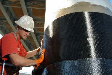 Men applying Sika CarboDur carbon fiber plates for structural strengthening