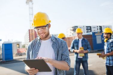 Group of smiling builders men in hardhats with tablet outdoors on construction site