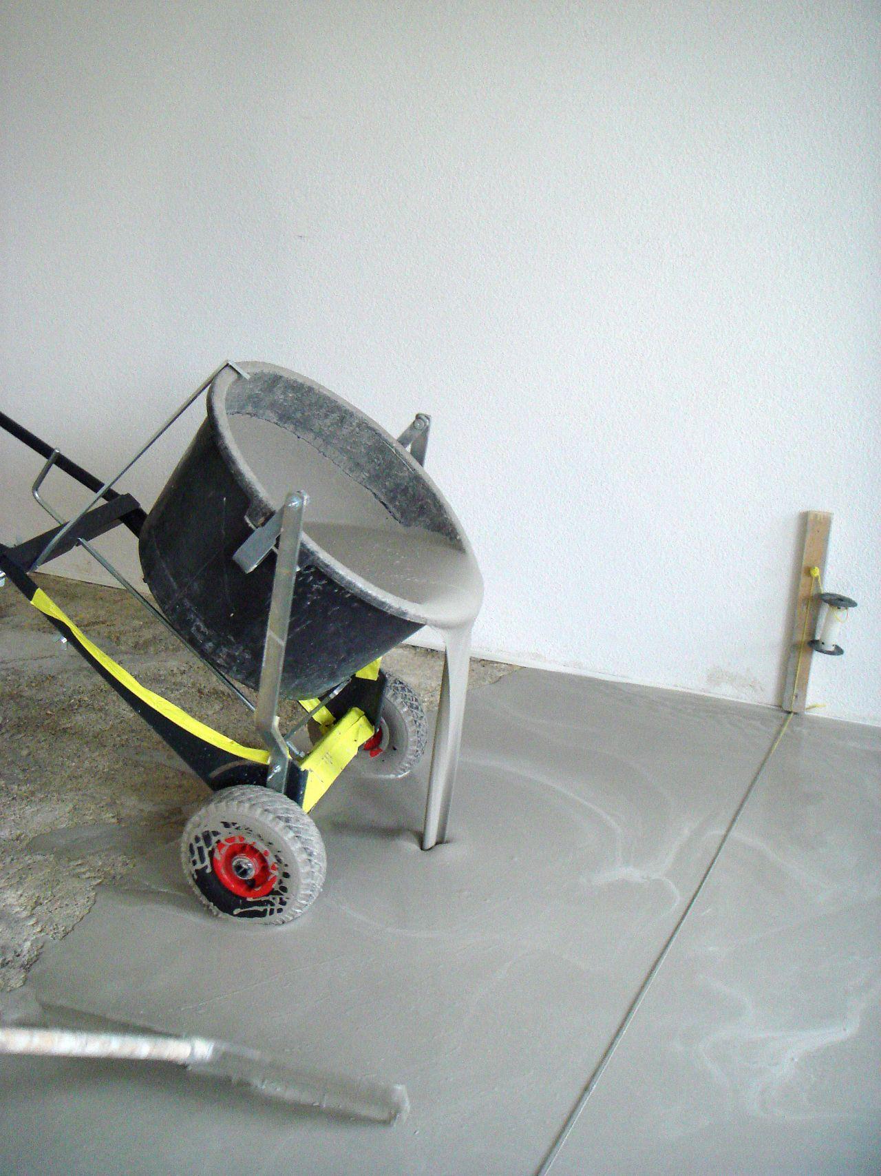 Sika applicator applying floor leveling from yellow bucket to shiny floor