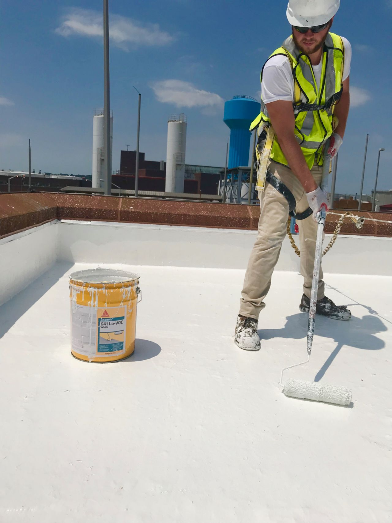 contractor applying Sikalastic 641 on a roof