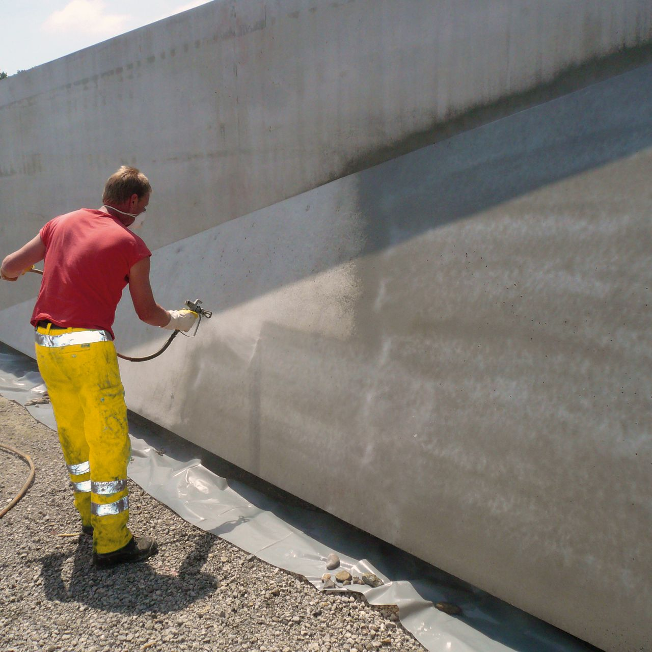 Man spraying concrete wall with Sikagard