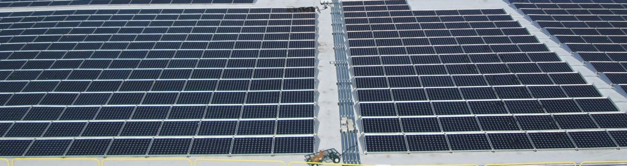 Rows of solar panels being installed on a roof with the SikaSola system.