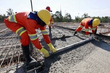 workers pouring cement in road construction on brazil