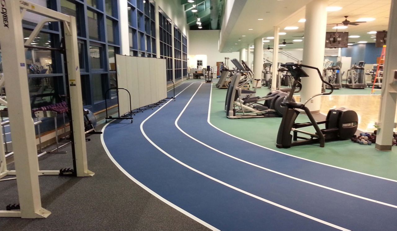 Inside a rehab facility, excersize equipment can be seen, and the floor has a track built into it.