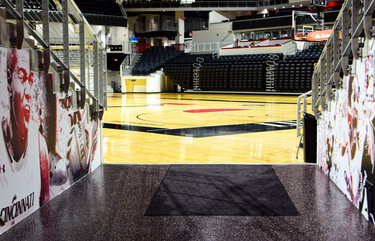The hall of a basketball stadium that transitions from court to stadium with a custom color-coated floor with team colors, bleachers crowd each side.