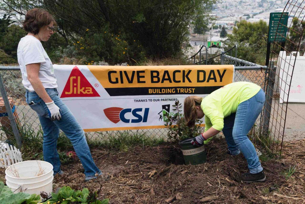 "Two woman planing plants in front of a banner that reads ""Sika Give Back Day"""