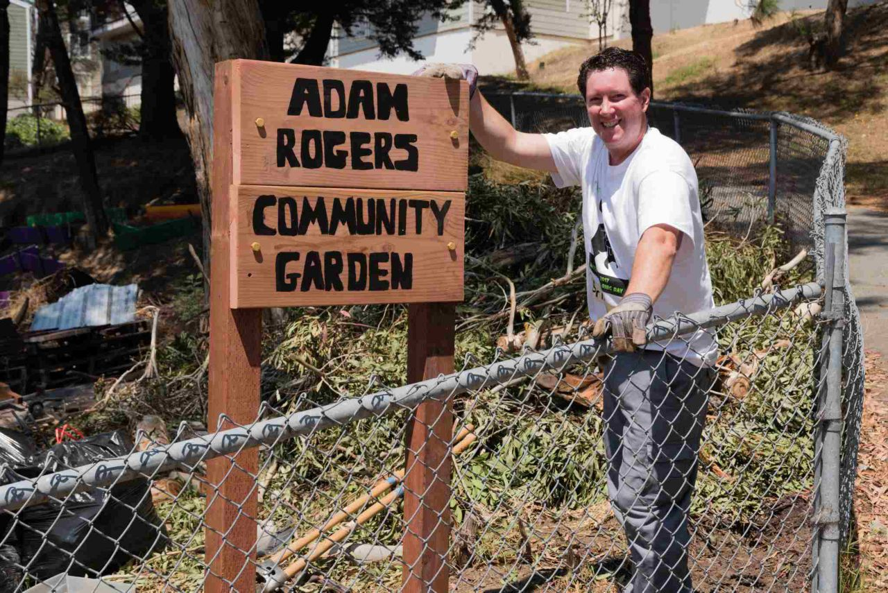 "A man standing next to a sign in a garden that reads ""Adam Rogers Community Garden"""