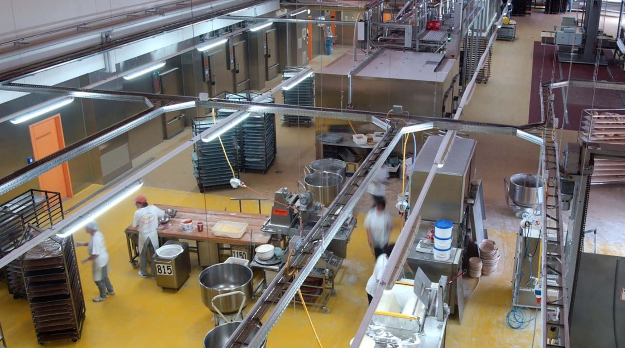The inside of a kitchen with equipment and tables, a PurCem floor is being shown on the ground.