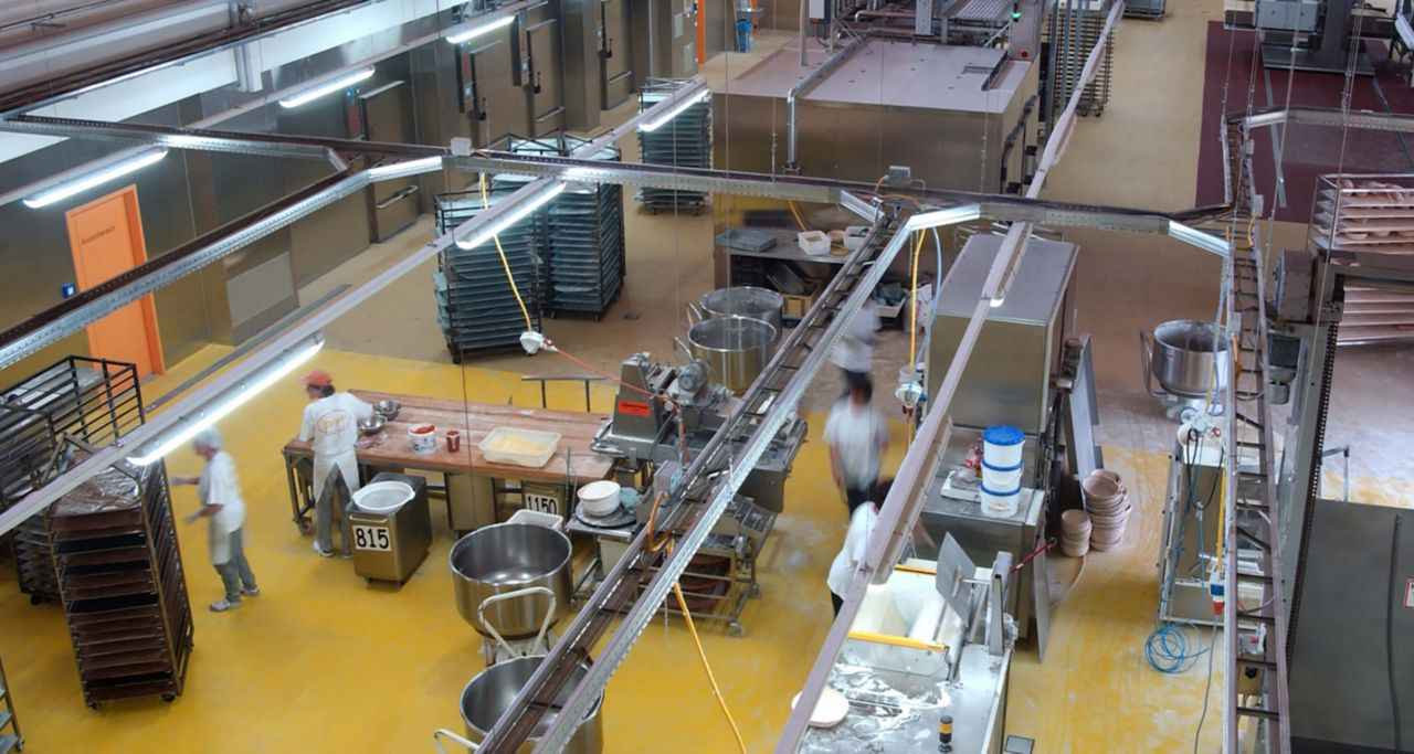 The interior of a kitchen using a PurCem floor, workers below work at various stations within the kitchen.