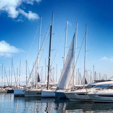 Marina with yachts and sail boats lined up in blue water.  Blue skies with clouds.