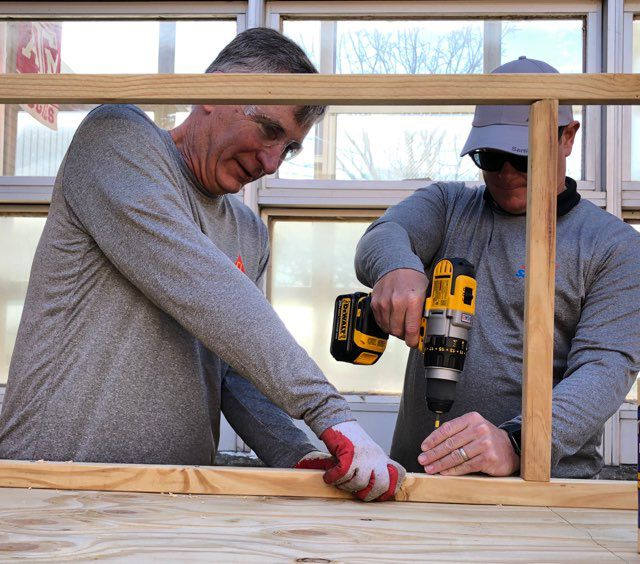 Two men working on wooden beams, one of them is holding the beam, and the other man is using a power drill.