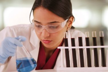 Latino scientist looking at liquids in vials