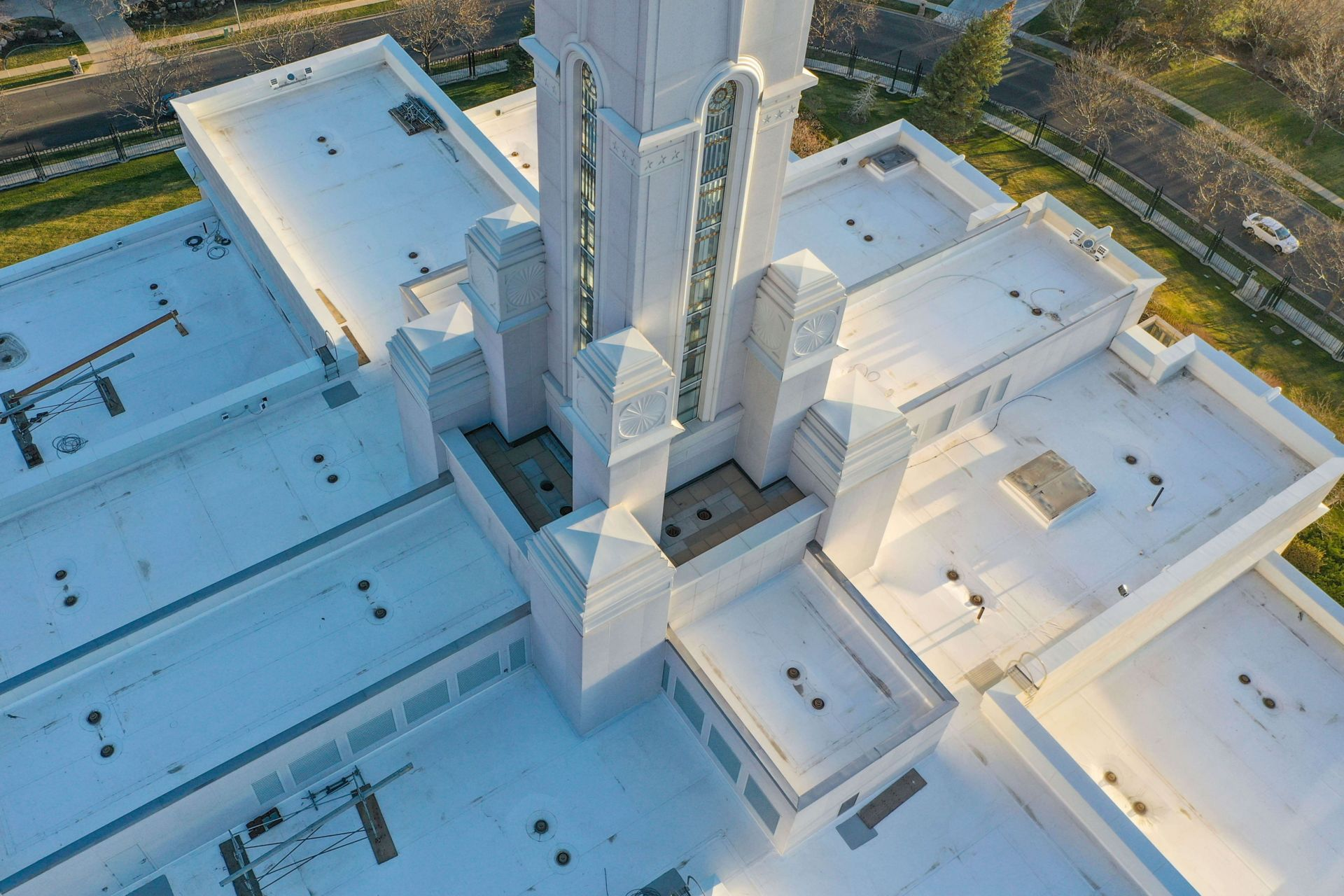 Close up aerial view of the Bountiful Temple with a spire in the center and white roofing membrane on the roof