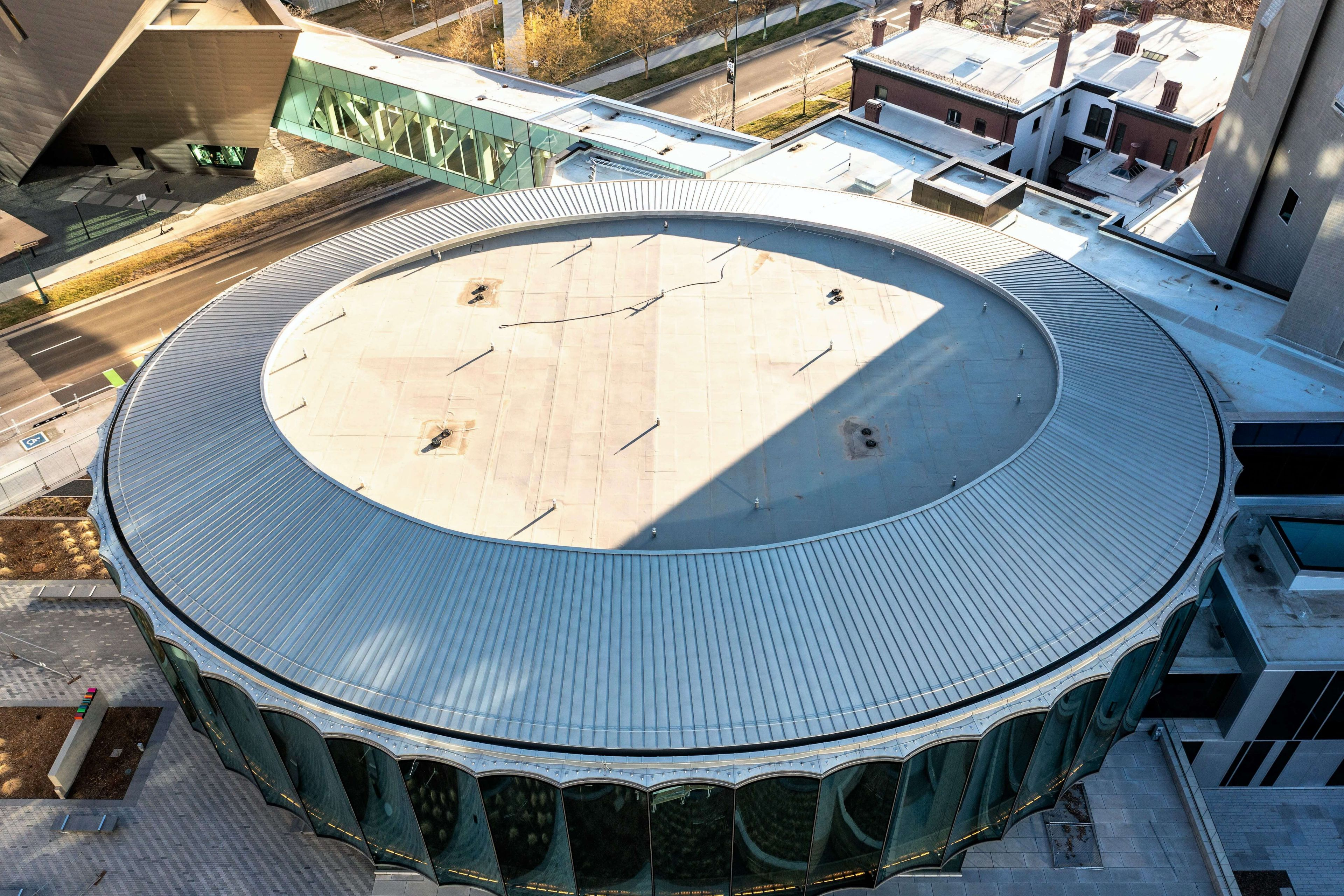 Aerial view of a section of the Denver Art Museum showing a white Sarnafil membrane on a circular roof with a ribbed roof outline