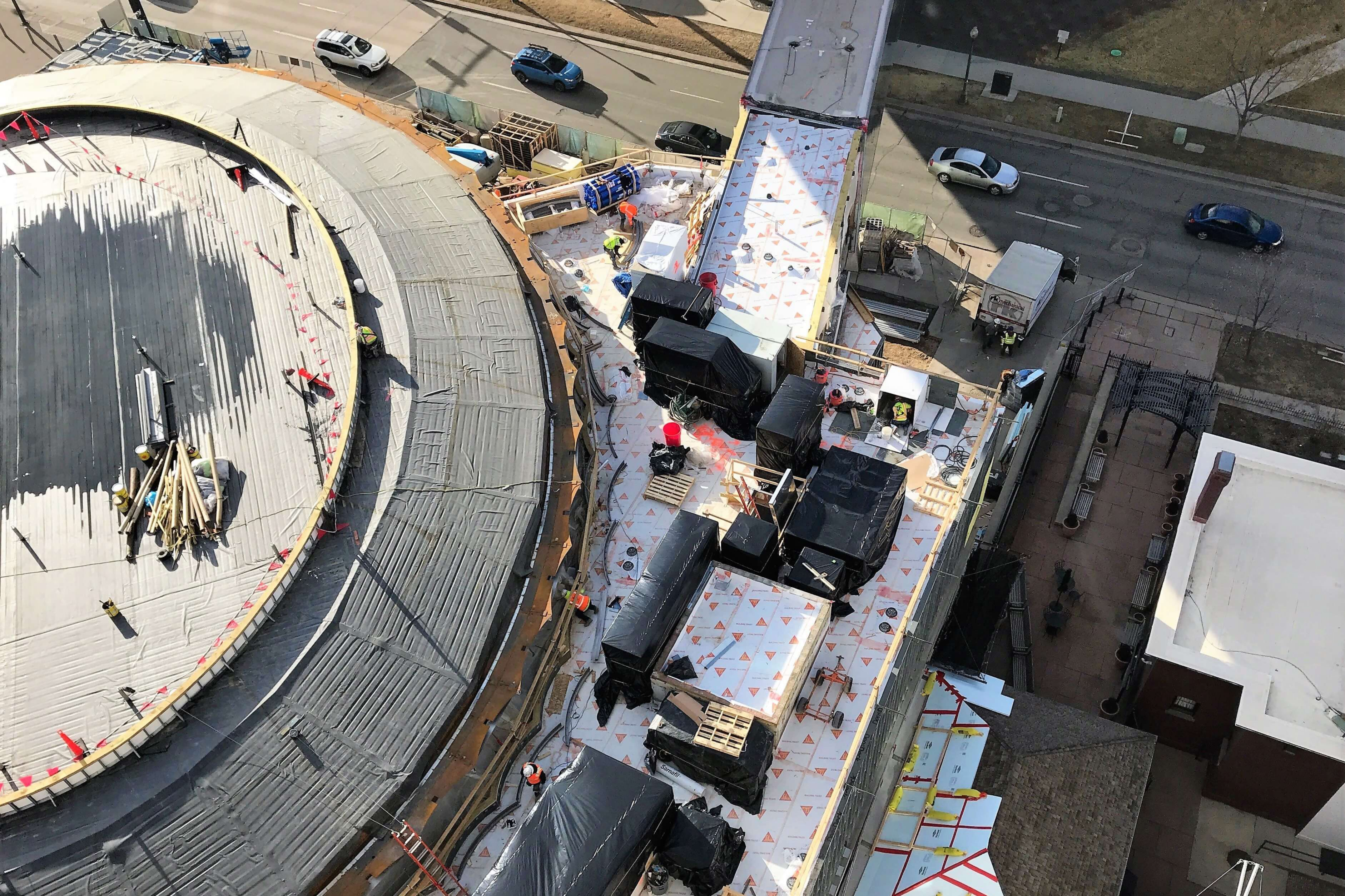 Aerial view of the Denver Art Museum while it is under construction. Workers can be seen laying down roofing membrane.