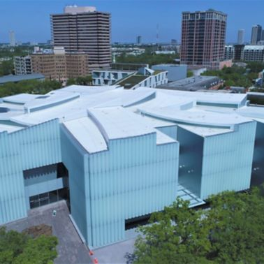 Aerial view of the Houston Museum of Fine Arts showing a white Sarnafil roofing membrane with a city skyline in the background.