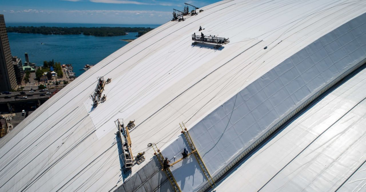 Construction workers on the top of the rodger center putting on white membrane with the ocean in the background