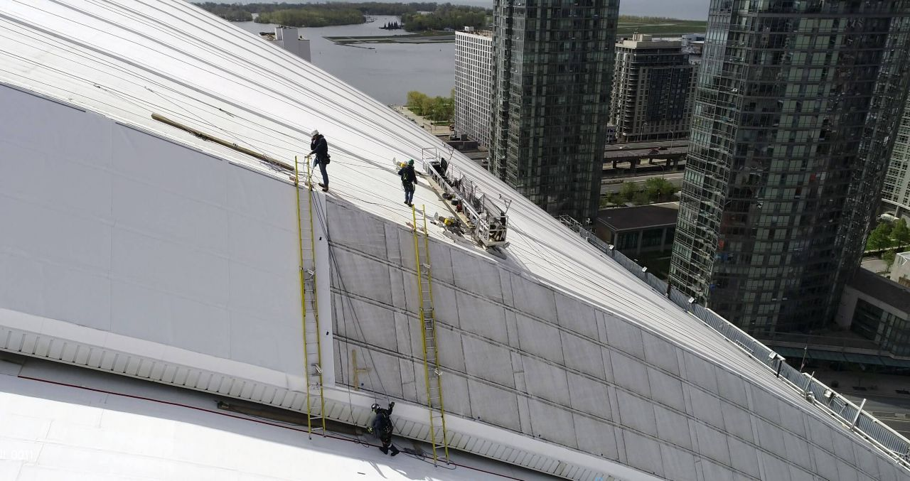 Construction workers on the top of the rodger center putting on white membrane