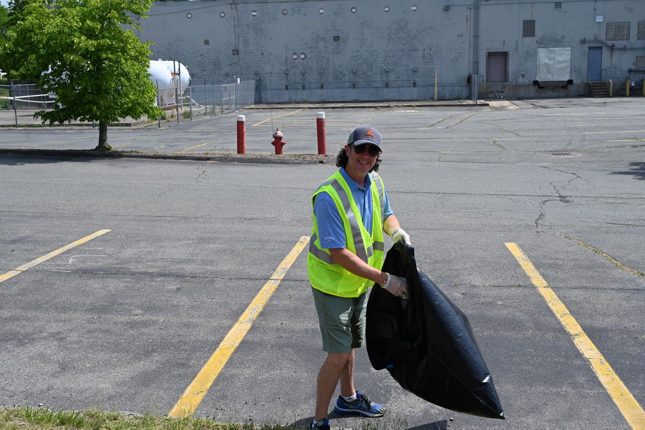 A Sika employee putting trash picked up from the side of the road into a trash bag