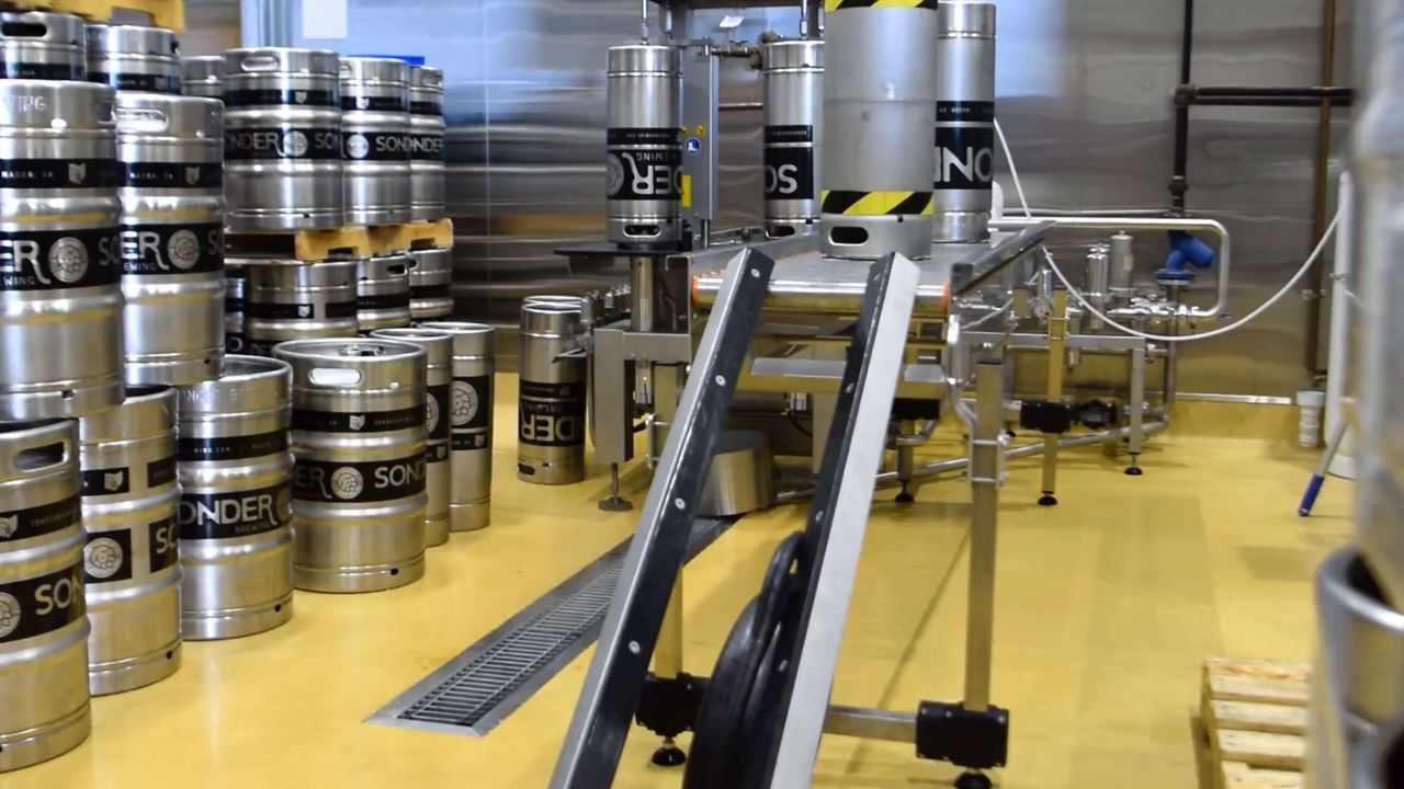 Inside a brewerie, with a machine hoisting up kegs. Stacks of kegs can be seen on the side.