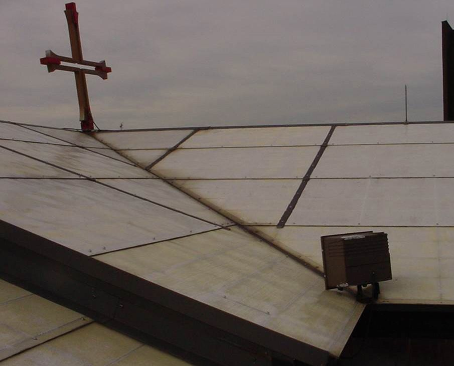 Exterior view of a roof with a cross perched on top