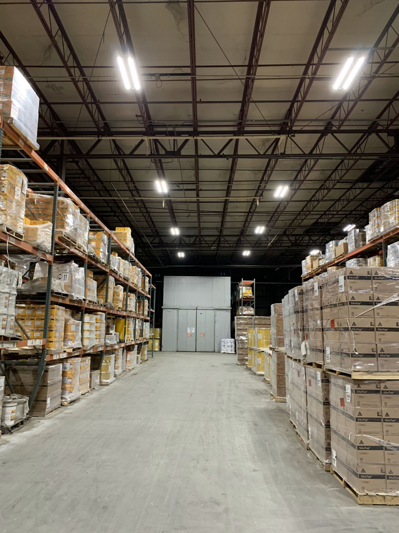 Large metal warehouse shelves forming an isle in a warehouse