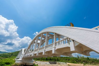 Old white railway bridge constructed against blue sky at Lamphun, Thailand.